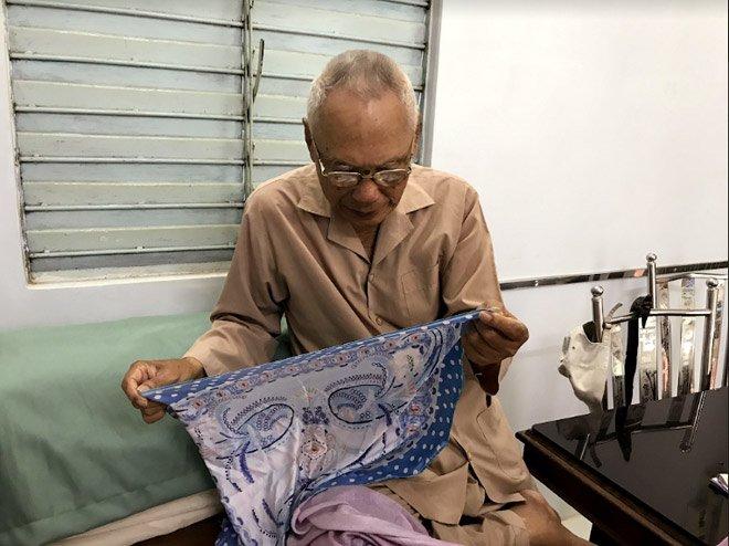 Nghệ nhân Tám Lăng đang xem xét chiếc khăn lụa Nhasilk